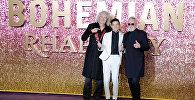 Американский актер Рами Малек позирует на красной дорожке с британским музыкантом, барабанщиком рок-группы Queen Роджером Тейлором и британским музыкантом, ведущим гитаристом рок-группы Queen Брайаном Мэйем на премьере фильма Богемская рапсодия на арене Уэмбли на севере Лондона. 23 октября 2018 года