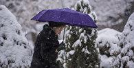 Женщина с зонтом идет по тротуару во время снегопада. Архивное фото