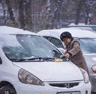 Женщина чистит лобовое стекло автомобиля от снега в Бишкеке. Архивное фото