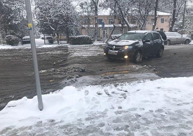 Автомобиль проезжает лежачий полицейский во время снегопада в Бишкеке