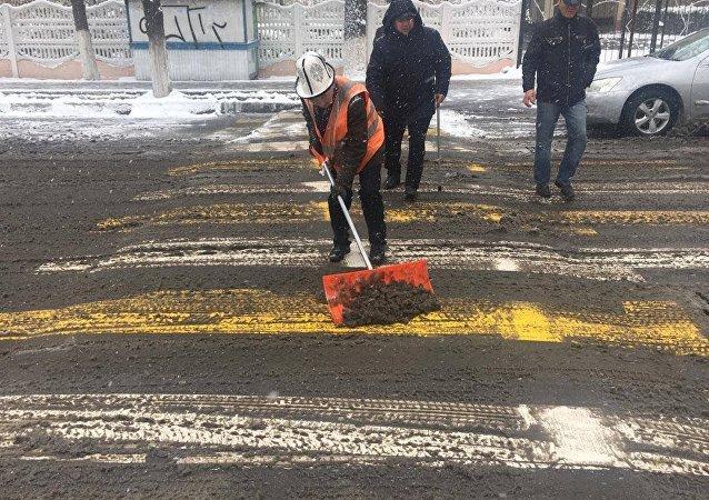 Сотрудники МП Тазалык чистят лежачий полицейский во время снегопада в Бишкеке