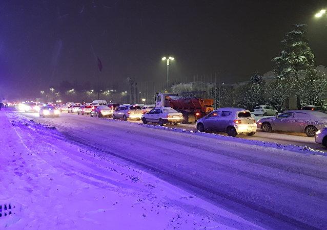 Автомобильный затор на проспекте Чуй во время снегопада в Бишкеке
