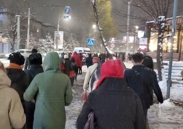Люди идут по тротуару во время снегопада в Бишкеке