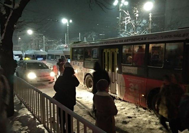 Горожане на остановке ждут транспорт во время снегопада в Бишкеке