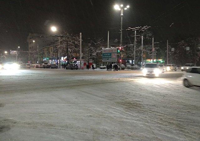 Пересечение проспекта Айтматова и улицы Ахунбаева во время снегопада в Бишкеке