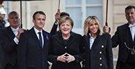 В центре слева направо: президент Франции Эммануэль Макрон, канцлер ФРГ Ангела Меркель и супруга президента Франции Бриджит Макрон у Елисейского дворца перед началом мероприятий, посвященных 100-летию окончания Первой мировой войны.