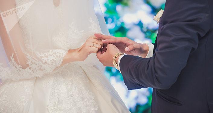 Невеста надевает кольцо жениху во время торжества бракосочетания. Архивное фото