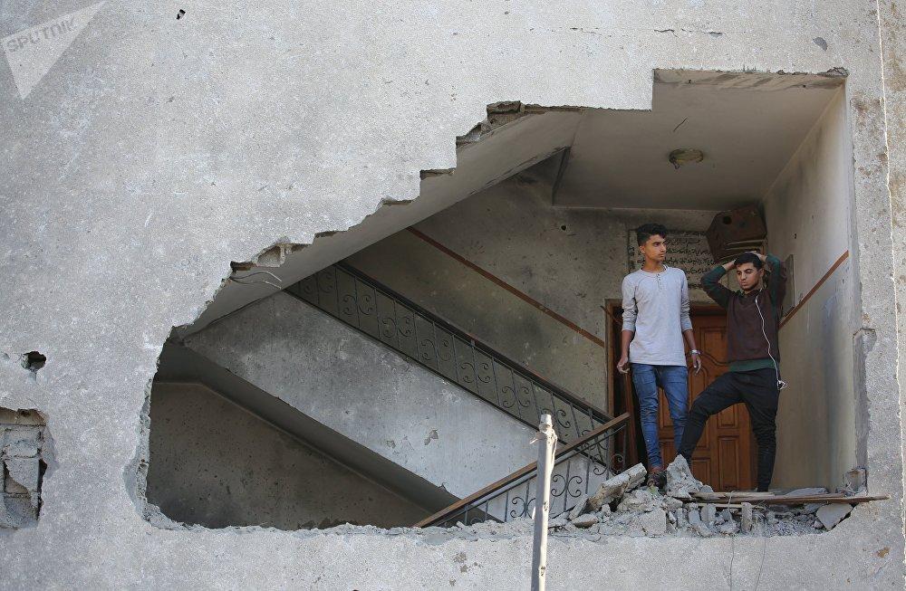 Газа секторунда Израилдин аскерлеринин ракеталык чабуулунан талкаланган имараттын ичиндеги жаштар