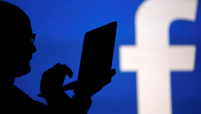 Человек сидит на фоне видеоэкрана с логотипом Facebook. Архивное фото