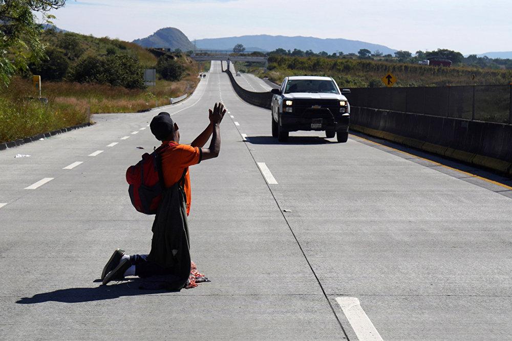 Борбордук Азиядагы мигрант Мексиканын кан жолунда АКШга бара жаткан автоунааны токтотууга аракет кылып жатат