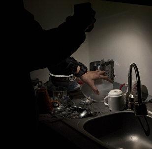 Мужчина в темноте освещает кухню мобильным телефоном. Архивное фото