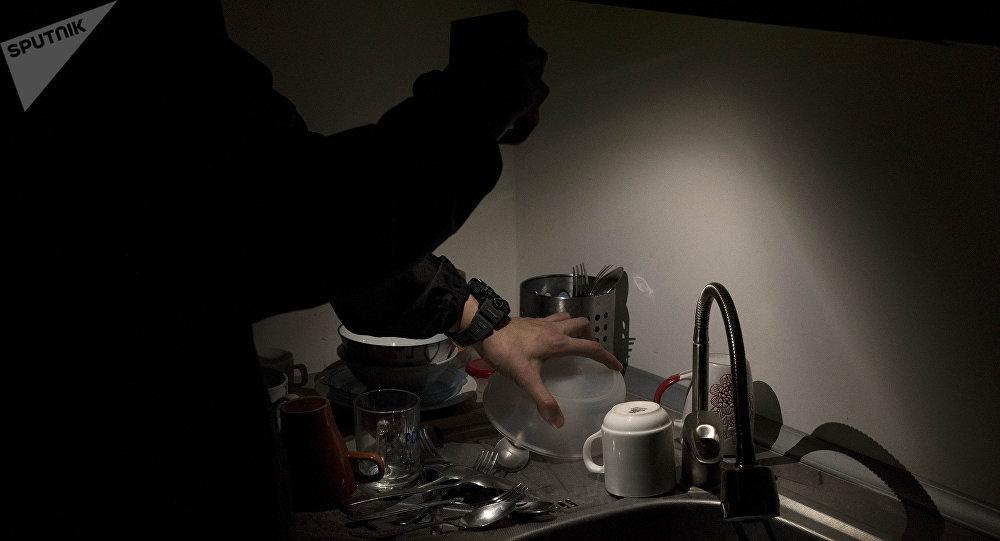 Мужчина в темноте освещает кухню мобильным телефоном