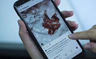 Девушка просматривает ленту фотосервиса Instagram на телефоне. Архивное фото