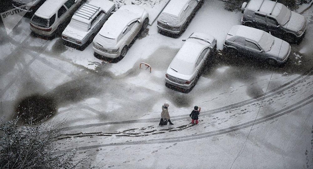 Женщина с ребенком идут по заснеженному двору. Архивное фото