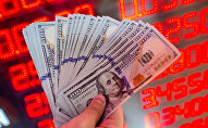Мужчина показывает долларовые банкноты в пункте обмена валюты. Архивное фото
