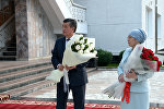 Президент Сооронбай Жээнбеков и первая леди Айгуль Токоева с цветами. Архивное фото