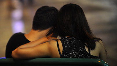 Парень и девушка сидят в обнимку. Архивное фото