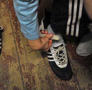 Мальчик одевает обувь. Архивное фото