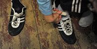 Мальчик одевает обувь. Архивдик сүрөт