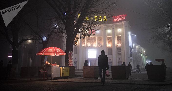Люди у кинотеатра Ала-Тоо во время густого тумана в Бишкеке