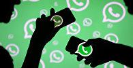 Люди с смартфонами с логотипом Whatsapp.Архивное фото
