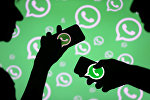 Силуэты людей на фоне логотипа WhatsApp. Архивное фото