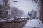Автомобильный транспорт движется во время снегопада в Бишкеке. Архивное фото