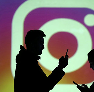 Силуэты людей на фоне логотипа Instagram. Архивное фото