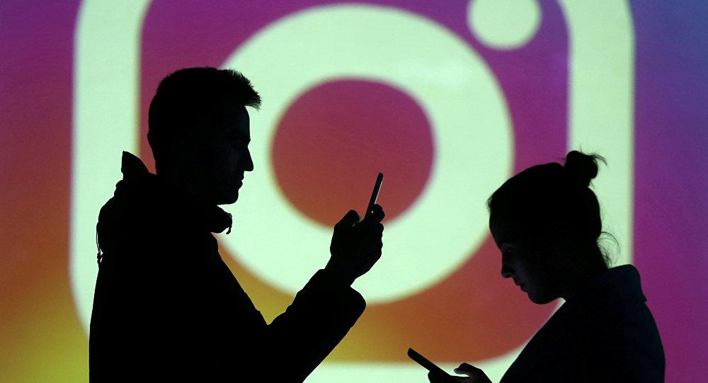 Силуэты мобильных пользователей на фоне логотипа Instagram. Архивное фото