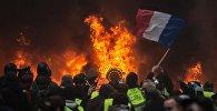 Участники протестной акции движения автомобилистов желтые жилеты, выступавшего с требованием снижения налогов на топливо, в районе Триумфальной арки в Париже.
