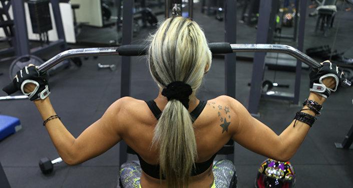 Девушка тянет вес в тренажерном зале. Архивное фото
