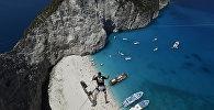 Мужчина прыгает с тарзанки со скал на пляже. Архивное фото