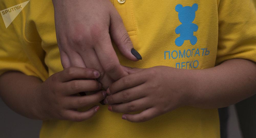 Мальчик с онкологическим заболеванием одетый в футболку с логотипом общественного фонда Помогать легко. Архивное фото
