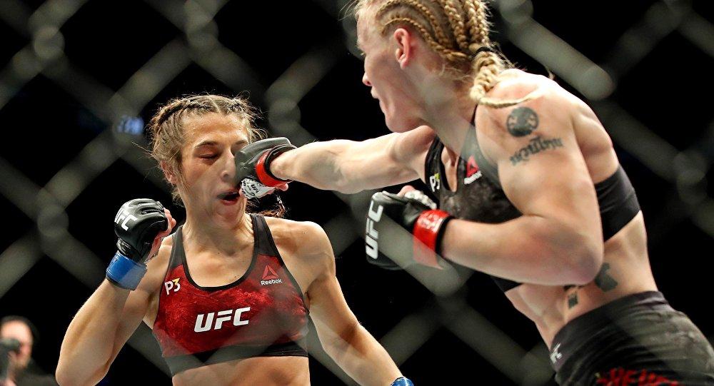 Кыргызстанка Валентина Шевченко наносит удар польской спортсменке Джоанне Енджейчик во время чемпионского боя на турнире UFC 231 в Канаде