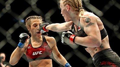 Кыргызстан Валентина Шевченко наносит удар польской спортсменке Джоанне Енджейчик во время чемпионского боя на турнире UFC 231 в Канаде