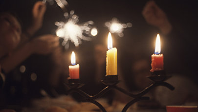 Семья зажигают бенгальские свечи в новогоднюю ночь. Архивное фото