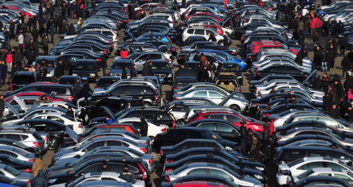 Люди выбирают автомобили на подержанном рынке. Архивное фото