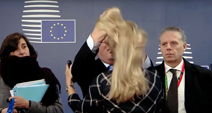 Кызматкер аялдын чачын уйпалап. Еврокомиссиянын президенти Юнкердин окуясы