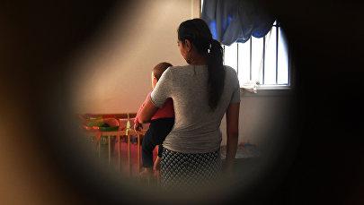 Женщина с ребенком стоит спиной. Архивное фото
