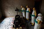 Медицинские работники дезинфицируют гроб, в котором находится тело человека умершего от вируса Эбола в Конго. Архивное фото