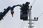 Электрики крепят провода на опоре линии электропередачи. Архивное фото