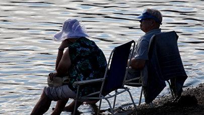 Пожилая пара на берегу озера. Архивное фото