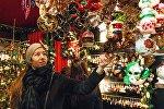 Женщина у прилавка с ёлочными игрушками на рождественской ярмарке. Архивное фото