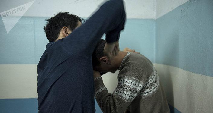 Мужчина бьет рукой другого. Иллюстративное фото