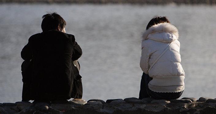 Пара сидит у озера. Архивное фото