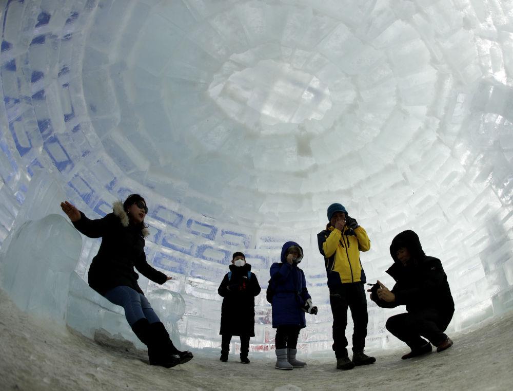 Люди фотографируются в иглу, построенном для зимних Олимпийских игр 2018 года в Пхенчхане (Южная Корея)