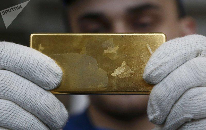 Сотрудник показывает золотой слиток на Приокском заводе цветных металлов в Касимове, Россия. 14 февраля 2017 года