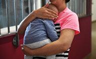 Женщина с ребенком в руке. Архивное фото