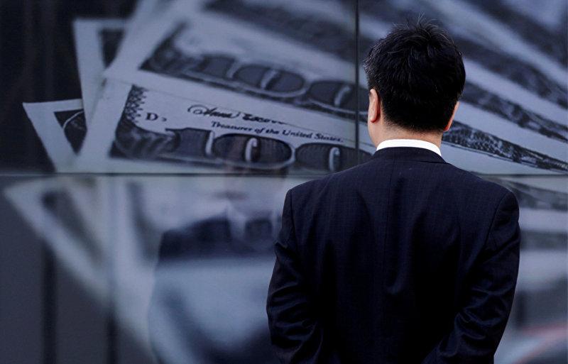 Бизнесмен смотрит на экран с фотографией банкноты США на сумму 100 долларов в Токио 8 апреля 2013 года