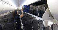 Стюардесса кладет багаж на полку. Архивное фото